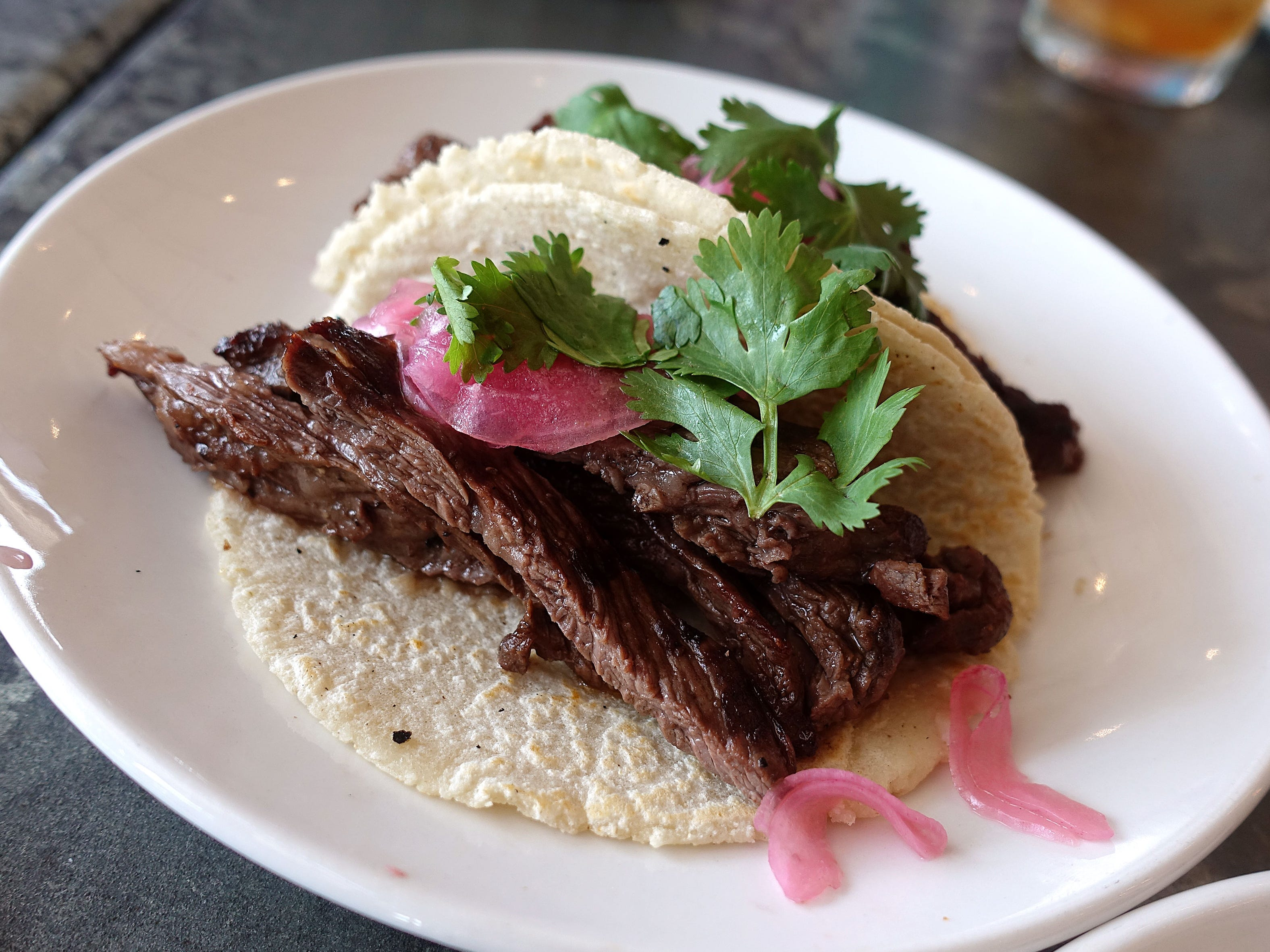 Steak tacos with cilantro and pickled red onion at Roland's Cafe Market Bar.