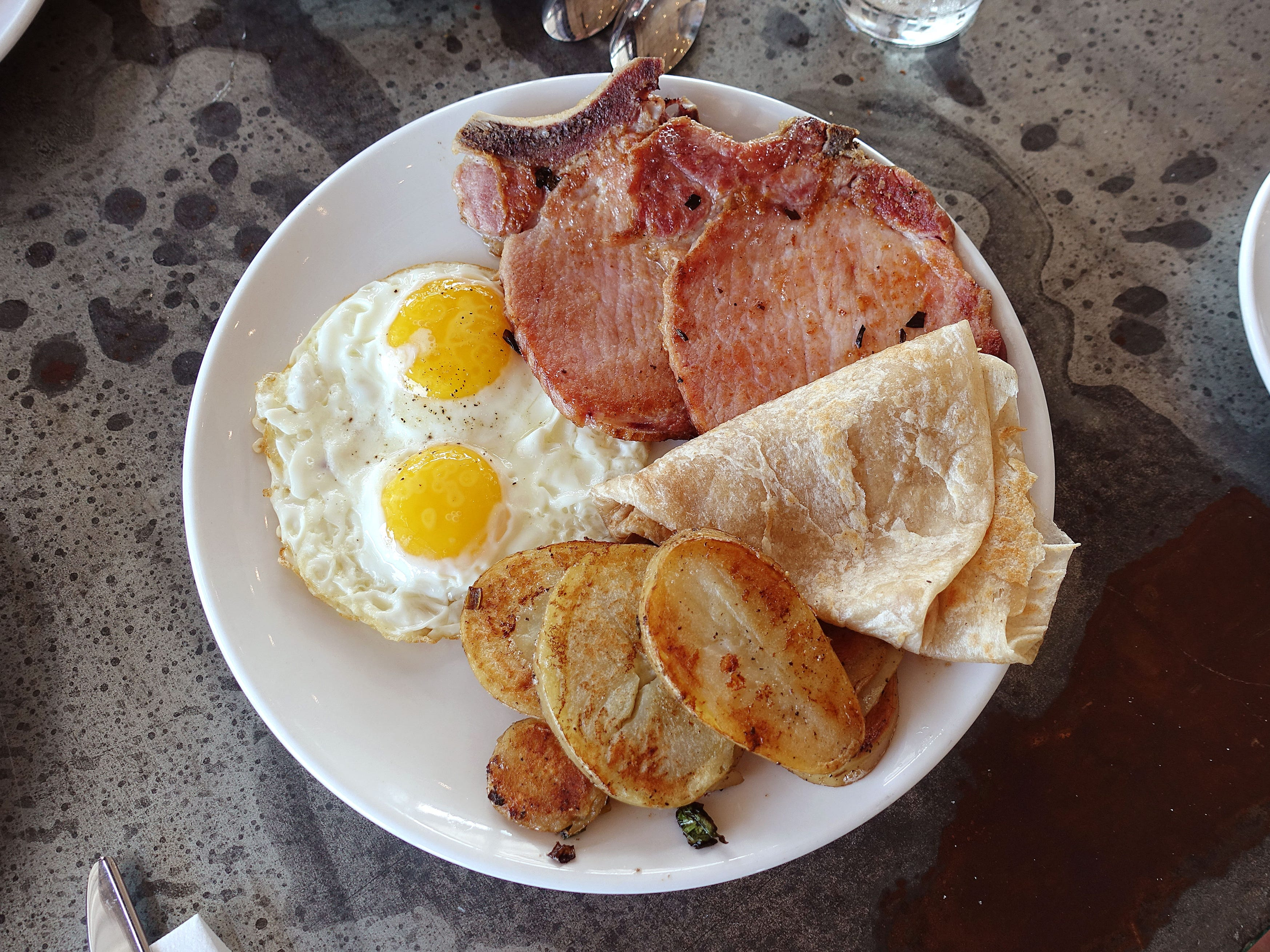 Niman Ranch pork chops with eggs, potatoes and flour tortillas at Roland's Cafe Market Bar.