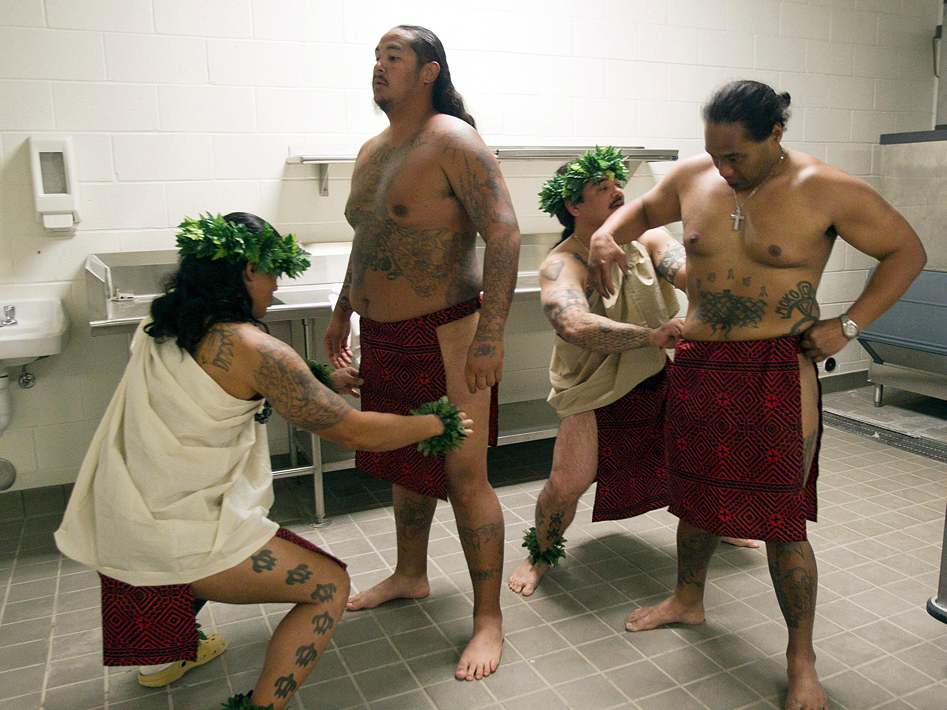 Inmates prepare to participate in a sunrise service wearing their traditional Hawaiian dress during the ceremonies on Oct. 9, 2011, to honor Lono, the Hawaiian god of rain and fertility, at Saguaro Correctional Center in Eloy. The private prison houses inmates from Hawaii serving lengthy sentences.
