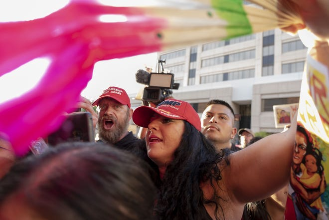 Trump supporters argue with Puente Human Rights Movement and Mijente's Chinga La Migra Tour protest with families impacted by immigration enforcement outside Maricopa County Sheriff Paul Penzone's office on Aug. 22.