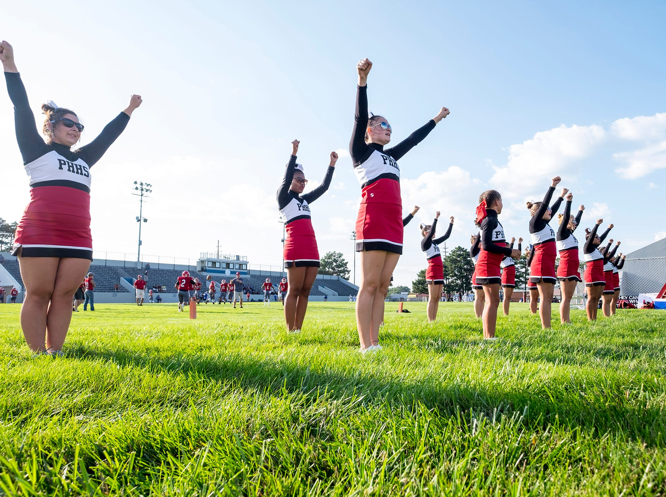 The Port Huron High School cheerleaders warm-up Thursday, Aug. 23, 2018, before the Big Reds' week 1 football game against Carman Ainsworth High School at Memorial Stadium.