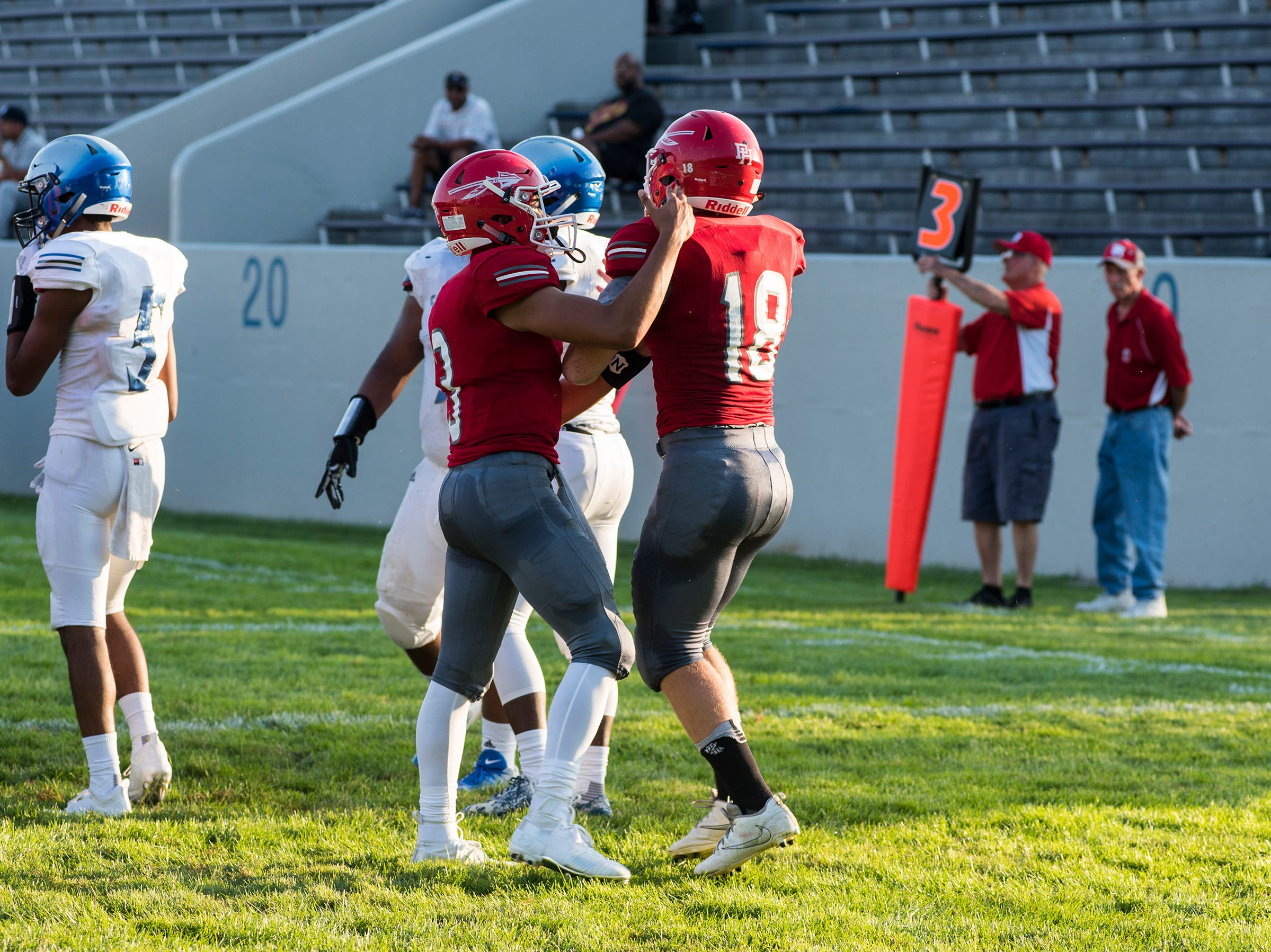 Port Huron High School quarterback Jonny Oriel (3) and running back Josh Butler celebrate after Butler scored the team's first touchdown during their game against Carman-Ainsworth High School Thursday, Aug. 23, 2018, at Memorial Stadium.