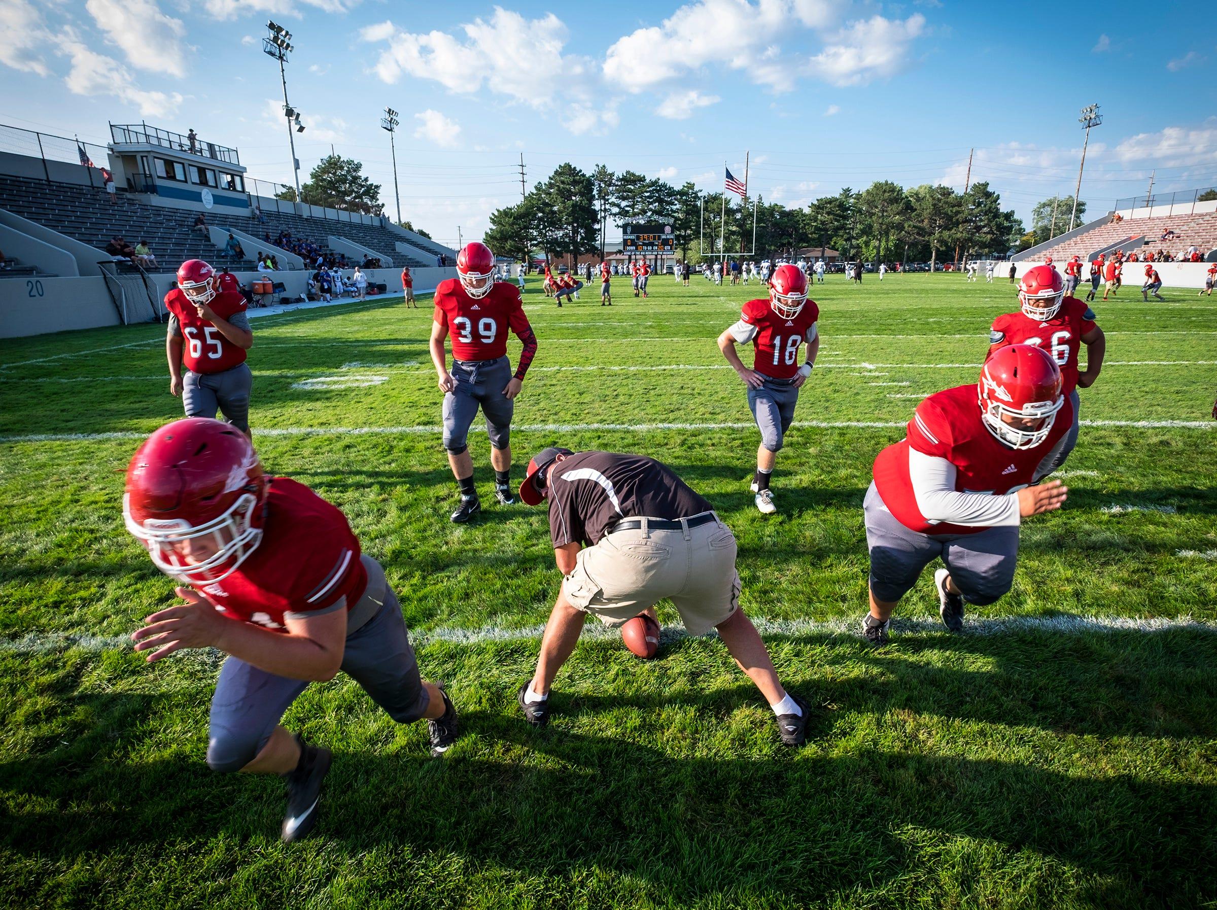 The Port Huron High School football team runs warm-up drills Thursday, Aug. 23, 2018, before the Big Reds' week 1 football game against Carman Ainsworth High School at Memorial Stadium.