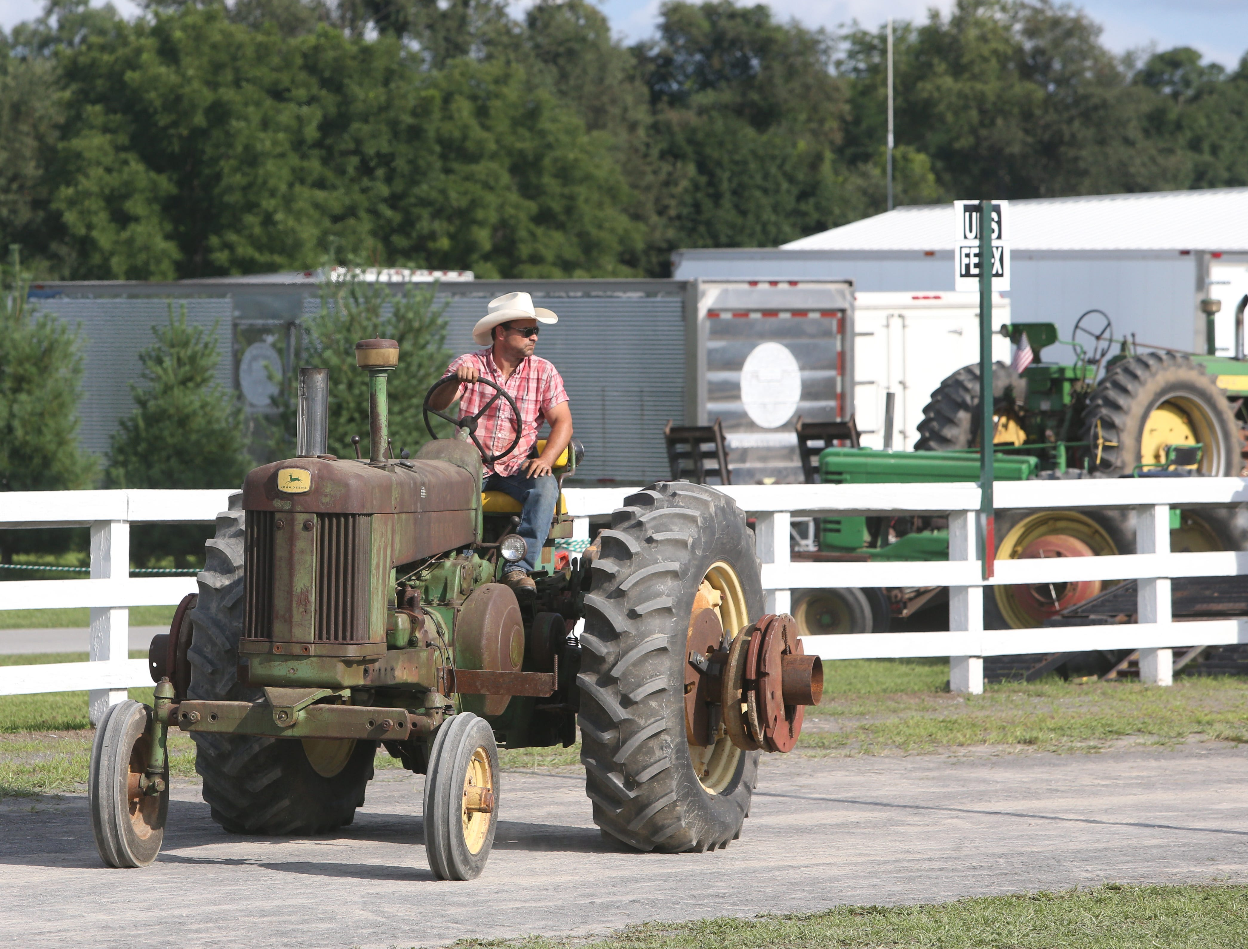 Kyle Mooney of Millbrook drives a vintage John Deere tractor at the Dutchess County Fair on August 21, 2018.