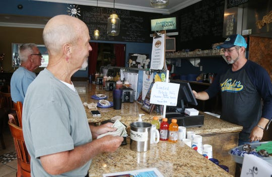 Bo Spencer of Bristol, Connecticut pays his check with owner, Pete Newman at Noshi's Coney Island Hot Dogs on Main Street in the City of Poughkeepsie on August 22, 2018.