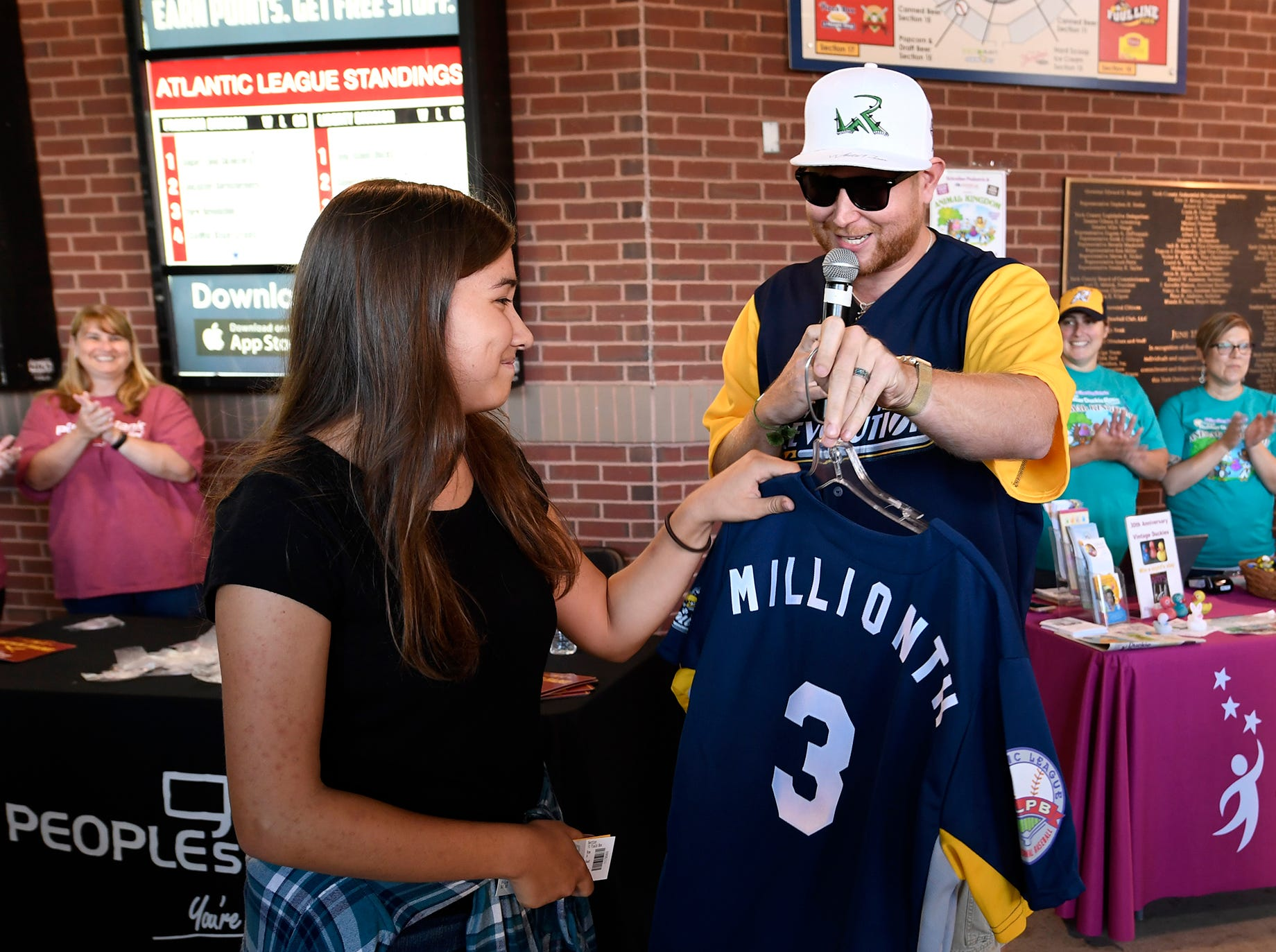 Rev's on-field host Eric Hartman, right, presents Courtney Kmett, 15, with the 3,000,000th fan jersey before the Revolution's game against Lancaster, Thursday, August 23, 2018. The lucky fan received the special Revs jersey, a bat signed by the team and two season passes for 2019. Courtney and her family are home in York on break from Bangladesh, where the family serves as missionaries. John A. Pavoncello photo
