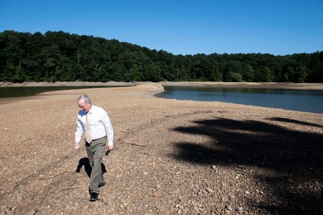 York Water Company chief operating officer J.T. Hand walks up the shore of Lake Williams, which is usually covered by water, on Thursday. The lake has been drained approximately 14 feet, in preparations for work on its 106-year old dam.