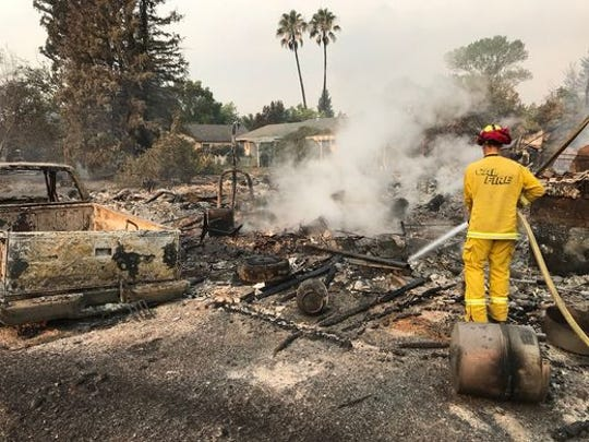 A Cal Fire firefighter hoses down hot spots at a Harlan Drive home that was destroyed by the Carr Fire.