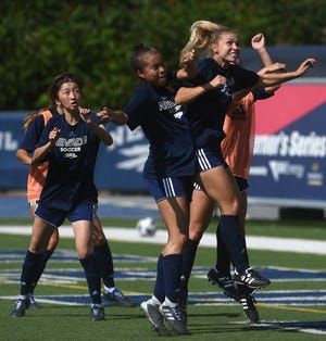 Nevada's Eleanor Small, right, goes up to head the ball during soccer practice at Mackay Stadium.