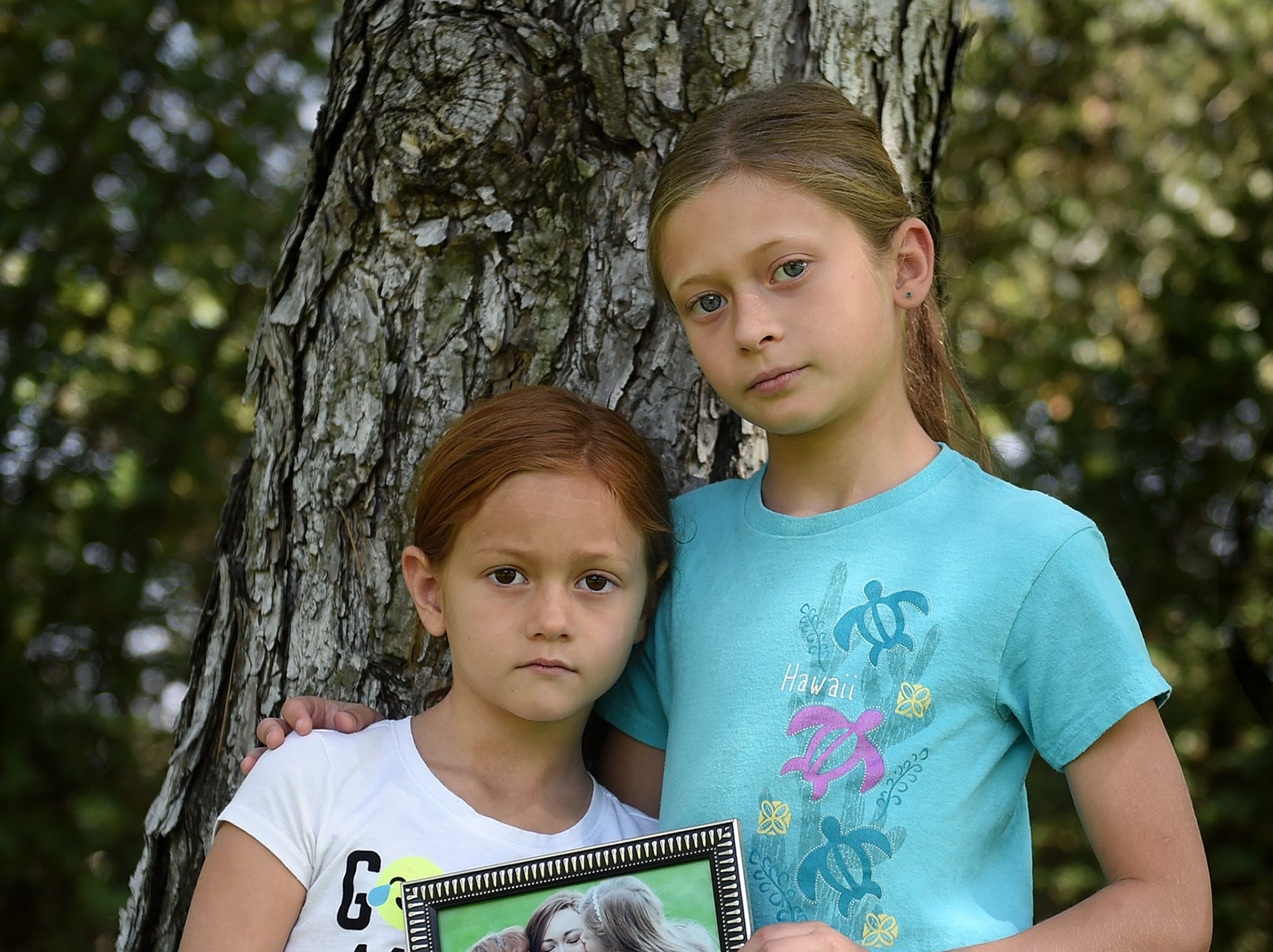 Holly, 7, left, and her sister Hannah Ephrom, 9, pose with a picture of their mom Sarah Herndon who died in January after a 4 year battle with cancer.