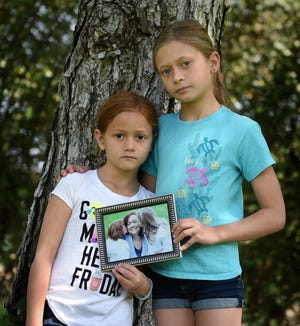 Holly and Hannah Ephrom, ages 7 and 9, pose with a picture of their mom, Sarah Herndon, who died in January after a 4-year battle with cancer.