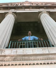 Paul Burgett, then dean of students at the University of rochester, stands on the porch of the Rush-Rhees Library.