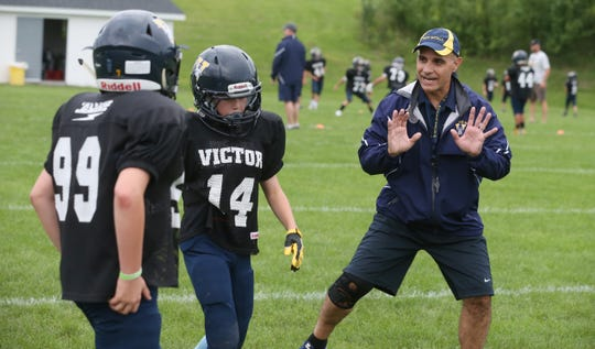 Coach Dave Tantillo never stops instructing his players on the right fundamentals in blocking and tackling during their Victor Youth League Blue B team practice Wednesday, Aug. 22, 2018 in Victor.  The team is made up of fifth and sixth graders.
