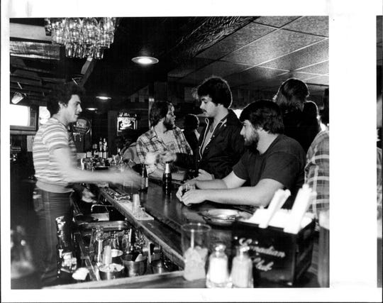 Bartender Bill Horn doing service on the early shift at the Elmgrove Inn on Lyell Road, Gates, in the 1980s.