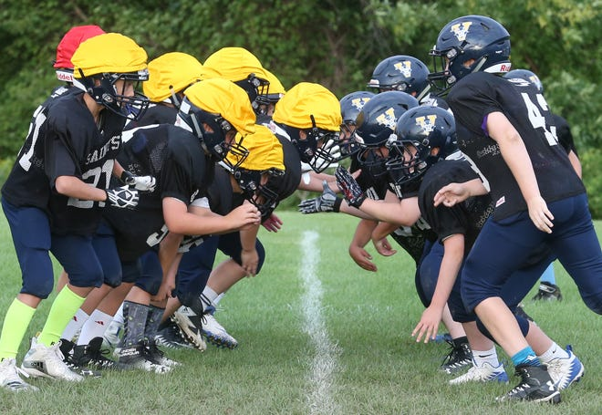 The offensive line, left, and defensive line, right collide at the line of scrimmage during the Victor Youth League Blue B team practice Wednesday, Aug. 22, 2018 in Victor.  The team is made up of fifth and sixth graders.