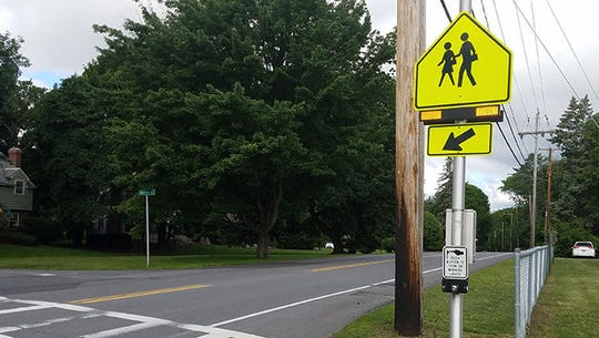 Flashing beacon sign at a crosswalk.
