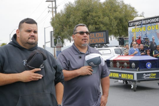 Tow truck drivers Derrick Perez, 47, and Oscar Bustamente, 35, recite the Pledge of Allegiance at the Spirit Ride, which reminds drivers to slow down and move over for first responders, including tow trucks.