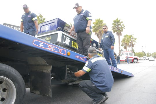 Tow truck drivers load up a casket symbolizing first responders killed while working on roadways.