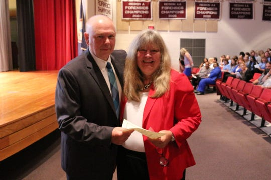 "Deborah Merrill of Arcadia Middle School is congratulated by Accomack School Superintendent W. C. ""Chris"" Holland for her 40 years of service to the school district, during a back-to-school celebration for Accomack Public School employees at Nandua High School in Onley, Virginia on Wednesday, Aug. 22, 2018."