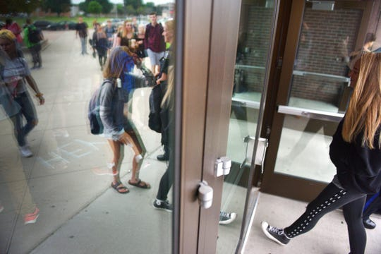 Roosevelt High School students walk in the front doors on the first day of school, Thursday, Aug 23, in Sioux Falls.