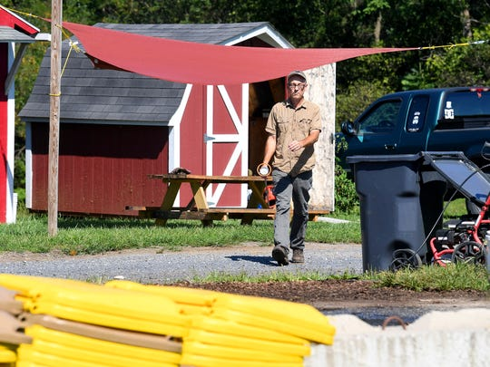 Eric Walter, president and chief composting officer of Black Bear Composting, carries a several foot thermometer as he heads out to take temperature readings of the various composting piles at their business site in Crimora on Thursday, August 23, 2018.