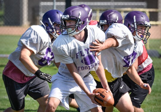 Players run through a play during practice Wednesday, Aug. 22, at Little Falls High School.