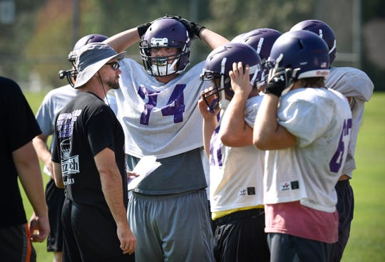 Head coach Joe Bartos talks to his players during practice Wednesday, Aug. 22, at Little Falls High School.