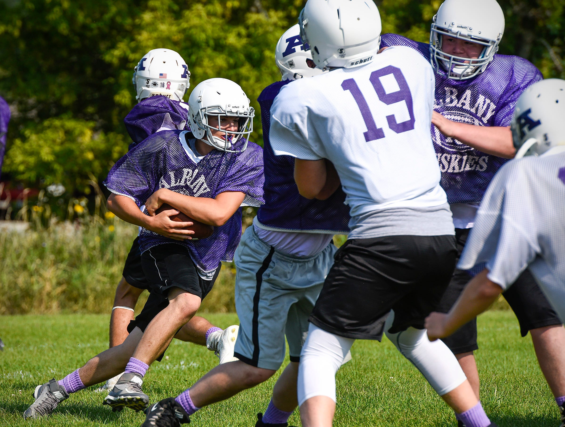 Albany Fullback Carter Kotzer cuts into the line with the ball on a play during practice Wednesday, Aug. 15, at the Albany High School.