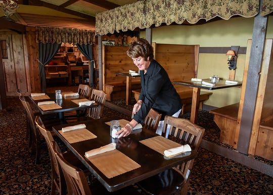 Mar Dols gets the dining room ready for lunch at Coyote Moon Grille Thursday, Aug. 23, in St. Cloud.