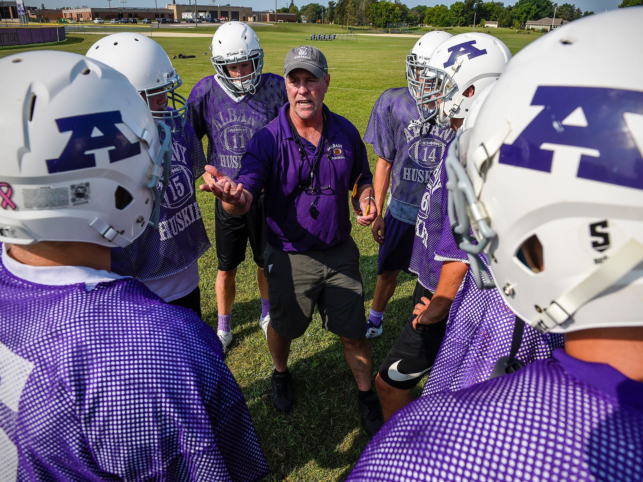 Albany coach Mike Kleinschmidt talks with players during a huddle Wednesday, Aug. 15, at the Albany High School.