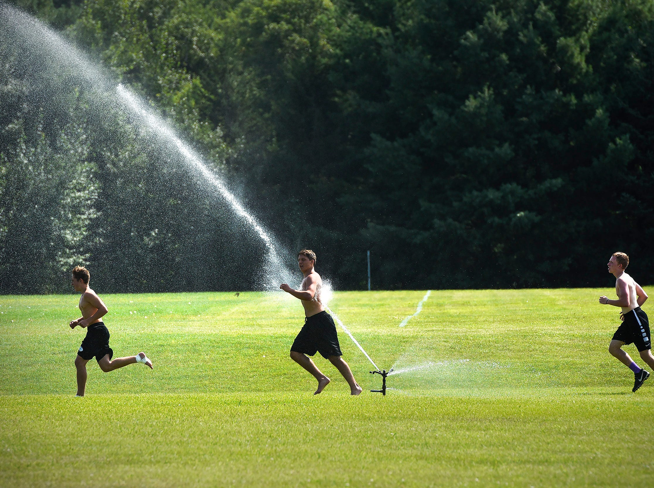 Coaches turn on the sprinklers for players as they run conditioning sprints after practice Wednesday, Aug. 15, at the Albany High School.