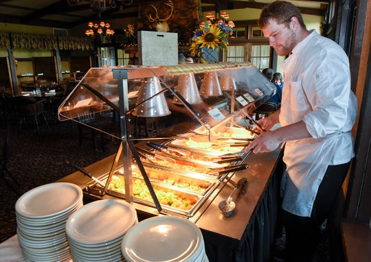 Kitchen manager Bill Ditlevson puts out the lunch buffet at Coyote Moon Grille Thursday, Aug. 23, in St. Cloud.
