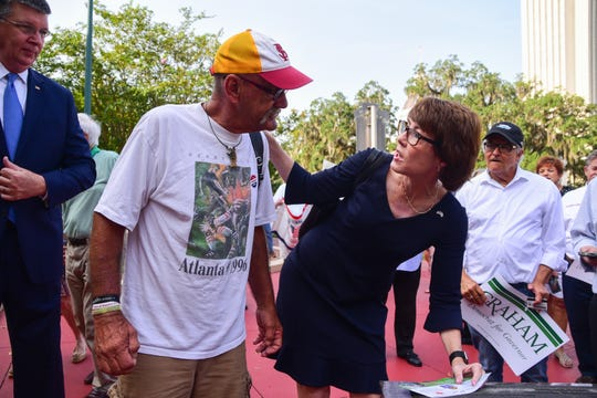 Florida Democratic gubernatorial candidate Gwen Graham signs an autograph for Ron Parfitt, a veteran and supporter of Graham, outside of the Leon County Courthouse.