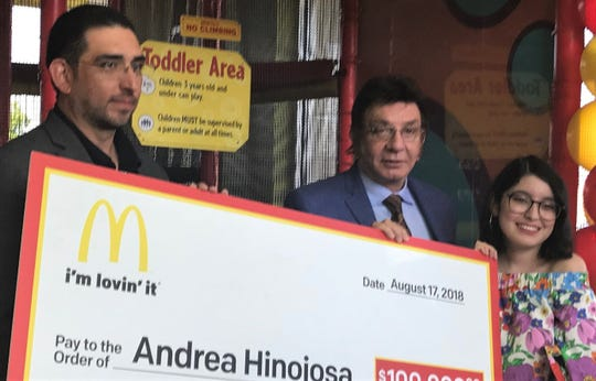 Andrea Hinojosa gets a $100,000 McDonald's HACER scholarship check from Richard Castro, center, and his son, Vincent Castro, owners of El Paso-area McDonald's franchises.