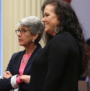 Assemblywoman Lorena Gonzalez Fletcher, D-San Diego, right, smiles as she and state Sen. Hannah-Beth Jackson, D-Santa Barbara, watch as the votes posted in the state Senate for passage of her forced arbitration bill, Wednesday in Sacramento. The bill would bar employers from requiring forced arbitration agreements, which compel employees to settle workplace complaints instead of going to court, as a condition of employment. The bill now goes to Gov. Jerry Brown.