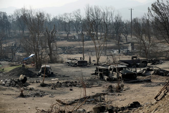 In this Aug. 11 photo, burned out cars sit in a neighborhood burned in the Carr Fire in Redding. Fire crews have made great gains against the Carr Fire, which has been burning for more than a month in Northern California.