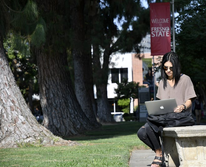 A Fresno State student works on her laptop before class on the first day of the fall semester on Thursday, August 23, 2018.