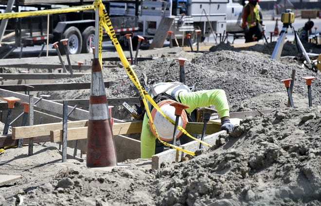 A construction worker digs on the corner of Goshen Avenue and Demaree Street on Thursday, August 23, 2018. Work at the intersection will last until at least February.