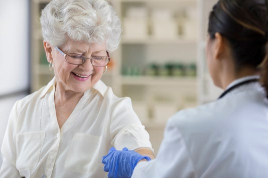 Senior Pharmacy Customer Gets A Band Aid After Flu Shot