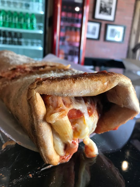 The OG PizzaRitto, a rolled up cheese pizza made with chicken, meatballs, mozzarella sticks, pepperoni, baked ziti and lots of cheese. Created at Russo's in Pearl River, it's become a viral sensation. Photographed August 23, 2018/