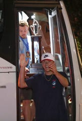 Nate Thomas carries the title trophy as Jack Dubecq steps of the bus while members of the American Legion World Series champions Post One are welcomed back to Delaware at Salesianum School Wednesday.