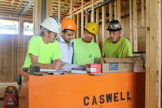 Rishen Patel (second from left), one of the owners of the new Holiday Inn Express in Middletown, looks over the building plans with some of the onsite construction managers from Harry Caswell, Inc. Pictured from left are: Bill Bennett, Patel, Adrian Naranjo and Charles Morton.