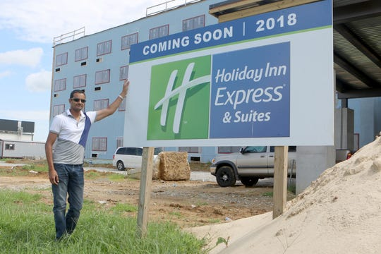 Rishen Patel stands by the sign announcing the opening of the hotel he and his family will open in 2019.