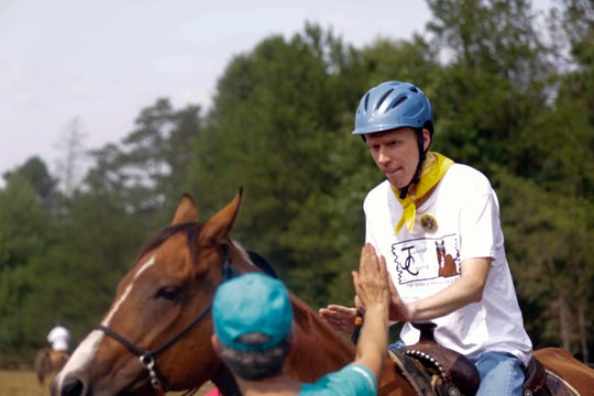 Curtis Schreier gets a high five from a volunteer after his ride during the Jeremiah's Crossing ride-a-thon Sunday, August 19, 2018.