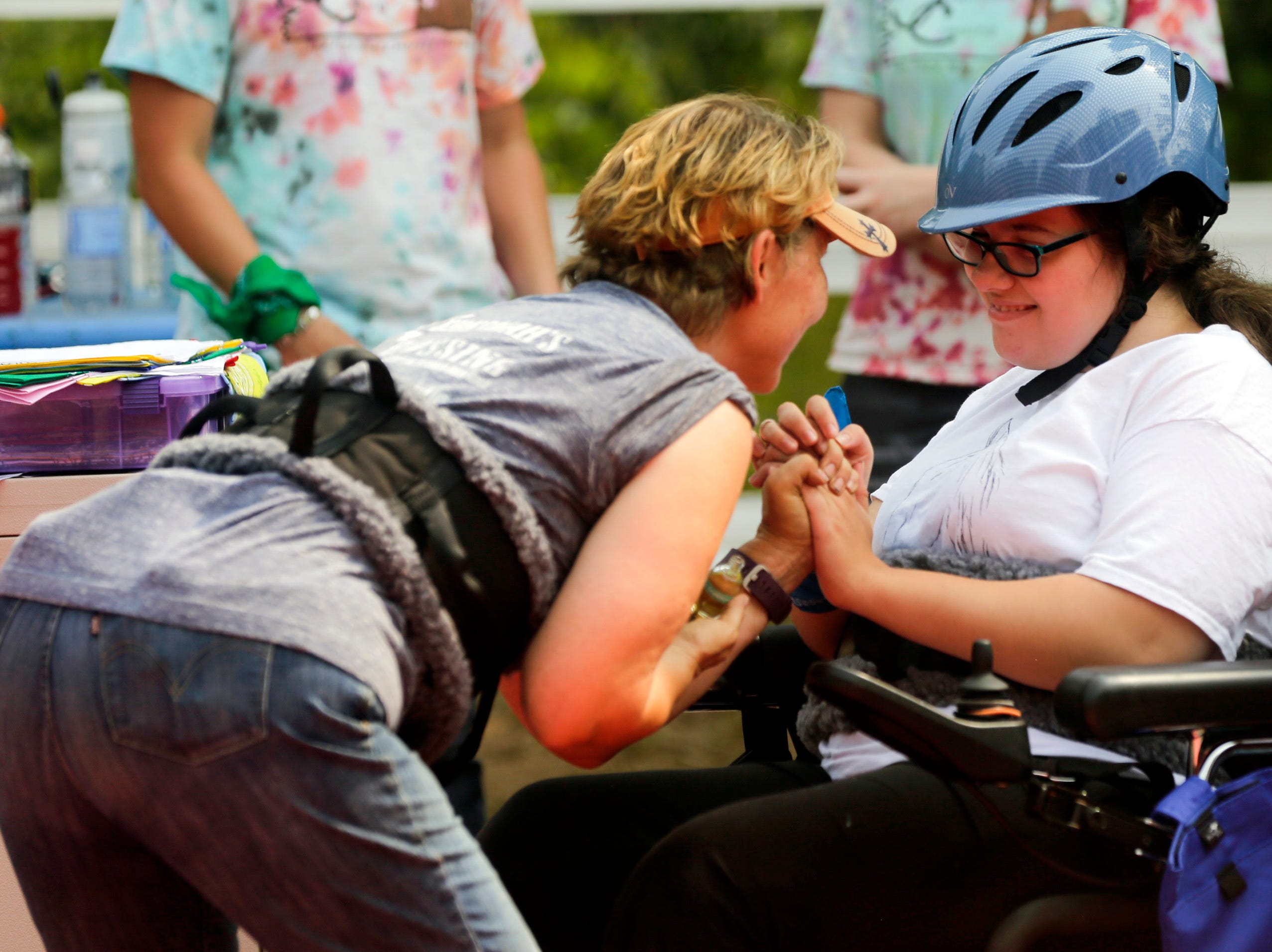 Kathleen Harris and Scedra Stoffel share a moment together before Harris helps Stoffel onto Alan, the horse that Stoffel regularly rides at Jeremiah's Crossing during their ride-a-thon Sunday, August 19, 2018 in Babcock, Wis.