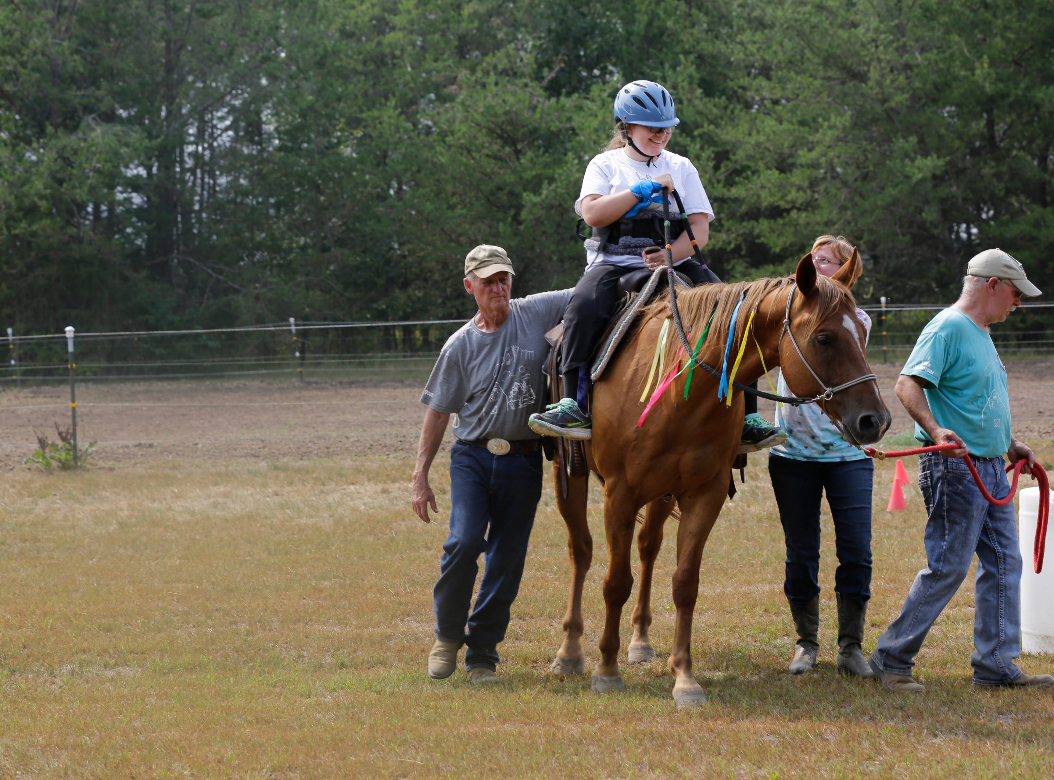 Scedra Stoffel smiles as she rides Alan, her regular horse, during the Jeremiah's Crossing ride-a-thon event Sunday, August 19, 2018 in Babcock, Wis.