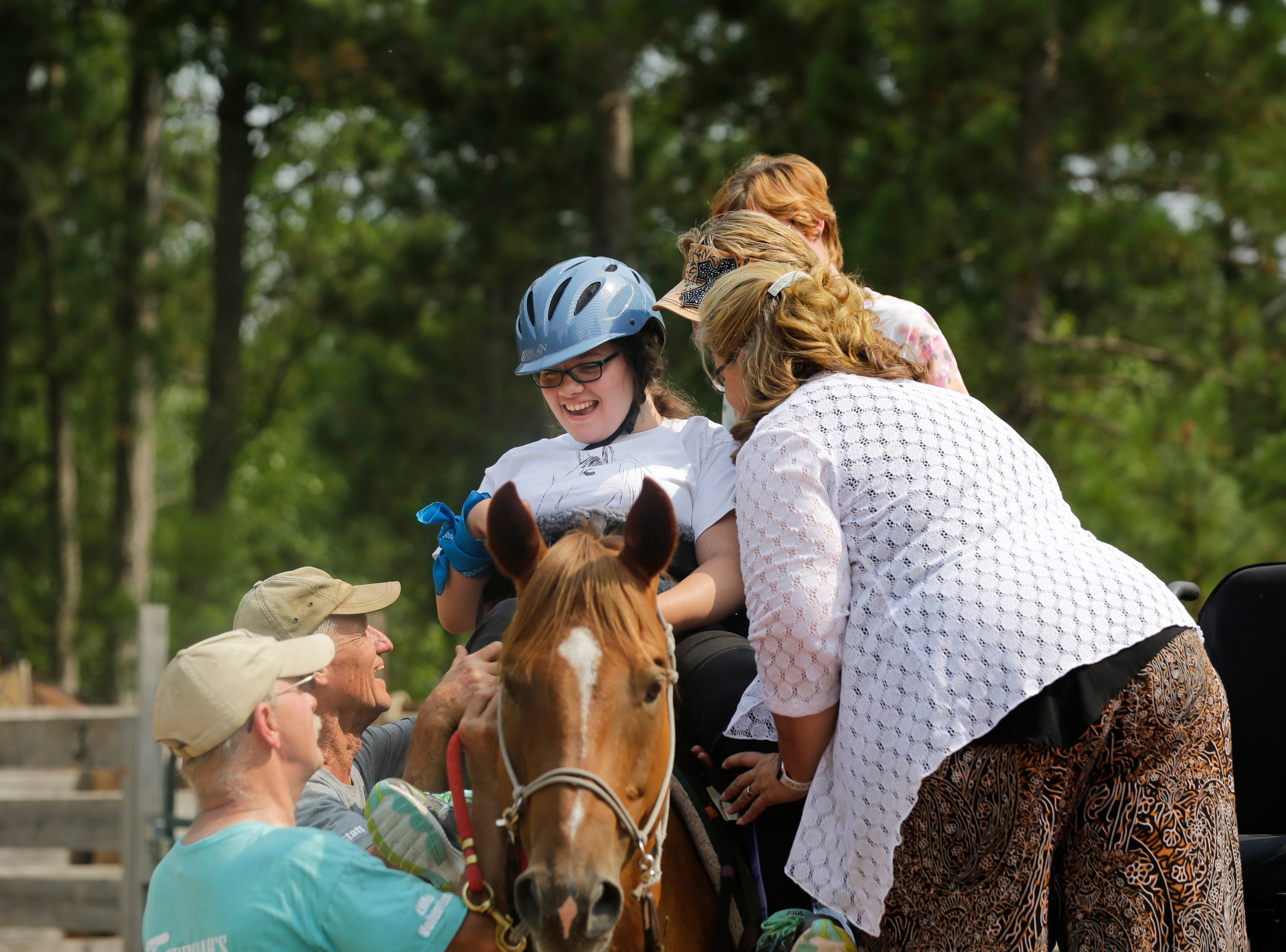 Scedra Stoffel smiles as she is helped onto Alan the horse by Kathleen Harris, her mother Julie Stoffel and three volunteers during the Jeremiah's Crossing ride-a-thon event Sunday, August 19, 2018 in Babcock, Wis.