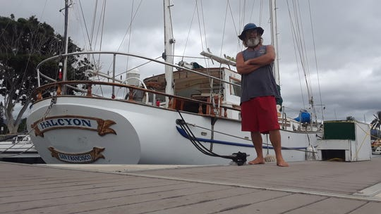 """Andrew Wheeler, a 16-year resident of Hawaii, who planned to ride out Hurricane Lane on the 41-foot sailboat he lives on. """"I'm pretty confident that by the time it gets to us it will be diminished to a Category 1 or a tropical storm,"""" Wheeler, a long-time scuba instructor, said. He's pictured here with his boat in a photo taken before Lane began bearing down on the islands."""