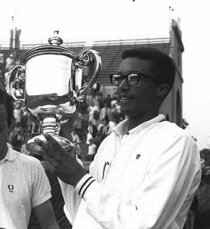 Arthur Ashe holds his trophy after defeating Tim Okker to claim his first U.S. Open Tennis Championship, in Forest Hills, NY,  on Sept. 9, 1968.