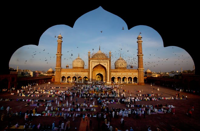Pigeons fly past as Muslims gather to offer Eid al-Adha prayers at the Jama Masjid in New Delhi, India, Wednesday, Aug. 22, 2018.